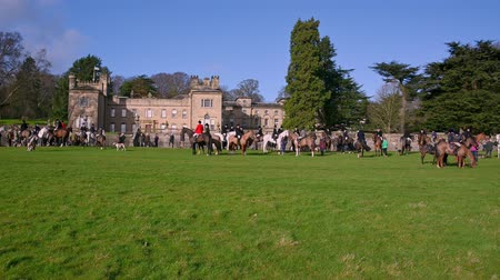 Aske Hall, Richmond, North Yorkshire, UK - February 08, 2020: Wide shot of horse riding fox hunters and spectators in front of Aske Hall and waiting for the hunt to begin