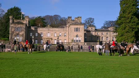 Aske Hall, Richmond, North Yorkshire, UK - February 08, 2020: Zoom in on Horse riding fox hunters, a pack of English Foxhounds and a number of spectators gathered in front of a traditional Georgian country house