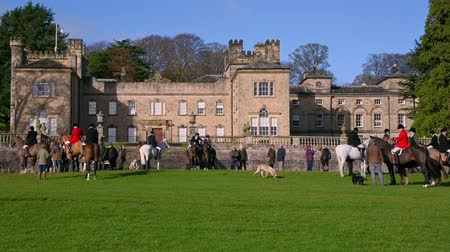 Aske Hall, Richmond, North Yorkshire, UK - February 08, 2020: Tight shot of Horse riding fox hunters and a number of spectators gathered in front of a traditional Georgian country house waiting for the hunt to begin