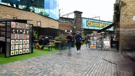 LONDON - SEPTEMBER 30, 2019: Time lapse of Camden Market with iconic bridge at the entrance as shoppers pass by diners in an outdoor eating area