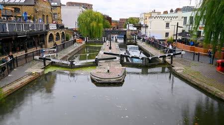 estreito : LONDON - SEPTEMBER 30, 2019: Long time lapse as a barge enters Camden Lock, rises up and exits as tourists watch Stock Footage
