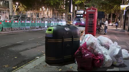 wysypisko śmieci : LONDON - SEPTEMBER 26,2019: Garbage bags full of trash piled up next to a bin and a traditional red telephone box at night with London Double Decker Buses passing