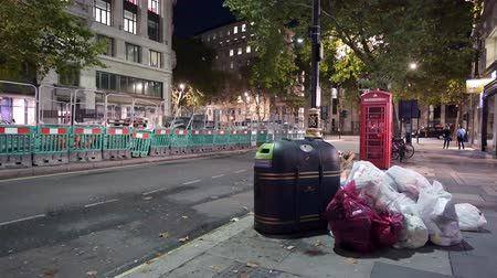 LONDON - SEPTEMBER 26,2019: Wide shot of bags full of trash piled up next to a bin and a traditional red telephone box at night with cars and roadworks in the background