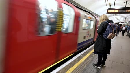 LONDON - SEPTEMBER 26,2019: Woman using smartphone as London Underground Tube train arrives at the platform