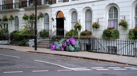 LONDON - SEPTEMBER 30, 2019: Zoom out from a pile of full bin bags on the pavement outside residential London townhouses Stock mozgókép