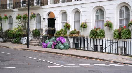 LONDON - SEPTEMBER 30, 2019: Zoom in to a pile of full bin bags on the pavement outside residential London townhouses as a couple walk past with young child in a pushchair