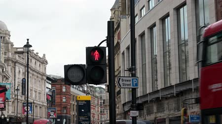 caution sign : LONDON - SEPTEMBER 27, 2019: Pedestrian crossing red man stop light signal on a busy London street as Double Decker buses pass by Stock Footage