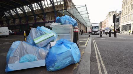 LONDON - SEPTEMBER 30, 2019: Lots of big blue bin bags full of rubbish overflowing from a large wheeled trash can outside Smithfield Market