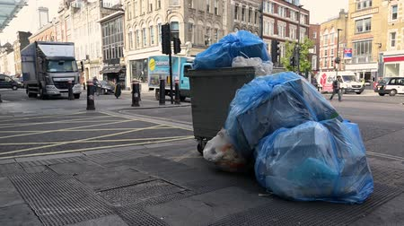 kutuları : LONDON - SEPTEMBER 30, 2019: Large, overflowing wheeled trash can with big blue bin bags full of rubbish next to it outside Smithfield Market Stok Video