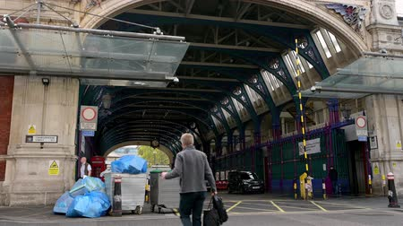 LONDON - SEPTEMBER 30, 2019: Two large wheeled trashcans overflowing with rubbish outside the archway entrance to Smithfield Market Stock mozgókép