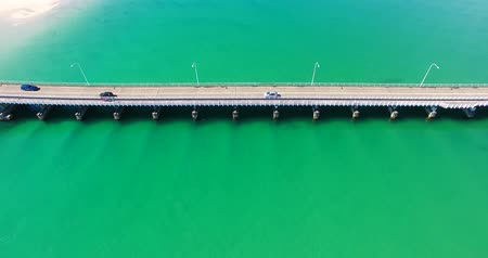 finest : Beautiful long bridge over a huge body of lush clear blue water with cars and people walking Stock Footage