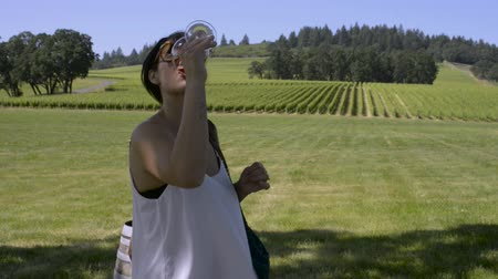 winogrona : Woman sipping a glass of Rosé wine, with a vineyard behind her Wideo