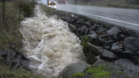 országúti : BEAVERTON, OREGON DECEMBER 9 2015, Water gushing out of a pipe into a roadside drainage ditch at capacity during heavy rains. Cars pass by on roadway Stock mozgókép
