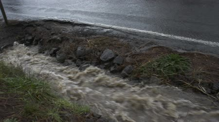 országúti : BEAVERTON, OREGON DECEMBER 9 2015, Water flowing into a pipe from a roadside drainage ditch at capacity during heavy rains. Camera pans right along ditch, tilts up to see Cars pass by on roadway Stock mozgókép