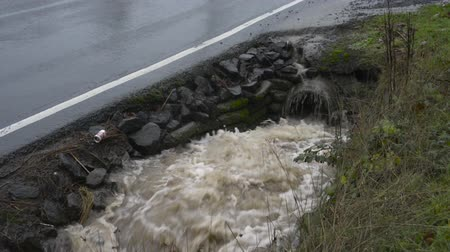 powódź : Water surging out of a pipe into a roadside drainage ditch, car passes by on the road