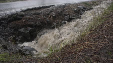 országúti : Storm water flowing from a roadside drainage ditch into a pipe, car passes by
