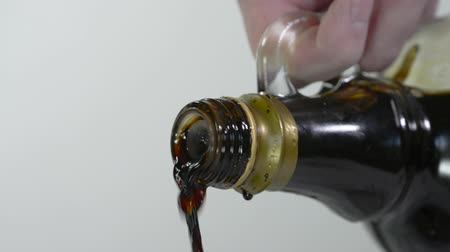 ocet : Pouring Balsamic vinegar in close up against a white background.