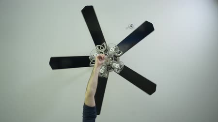 вентилятор : Hand using the pull cord to turn a Ceiling fan light on, camera directly below the fan, centered in the frame.
