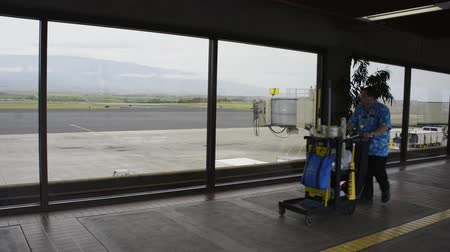 KAHULUI, HAWAII, FEBRUARY 28 2017, Walkway between gates in the Kahului Airport with large windows providing a view of the tarmac, and the hills beyond. A janitorial worker walks by with his cart.