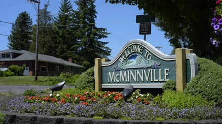 MCMINNVILLE, OREGON JUNE 06 2017, A roadside sign welcoming people to the city of McMinnville surrounded by planted flowers. Cars pass by  in the background.