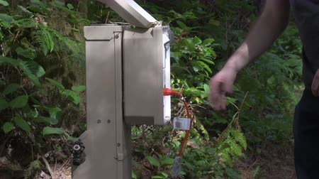 At a green, forested campsite, a hand lifting the cover of a power hookup box, unplugging a orange extension cord, and closing the lid. Stok Video