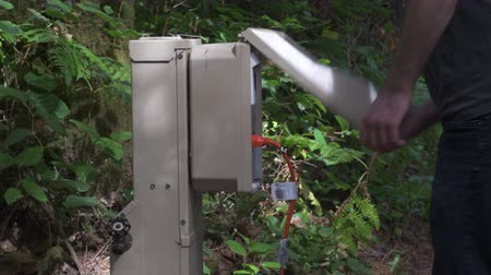 At a green, forested campsite, a person lifts the cover of a power hookup box, unplugging a orange extension cord, and closes the lid quickly.