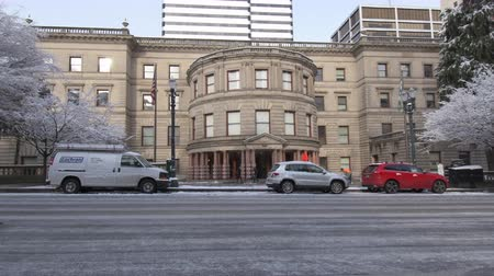 kormányoz : The Portland City hall building in the winter with a fine dusting of snow on it, trees covered. The road in the foreground covered in ice. Workers shoveling the pavement in front of the entrance.
