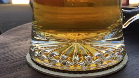 The bottom of a glass stein with golden colored beer, small carbonation bubbles rising from the center of the mug. Outside on a dark wood table.
