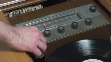 Hand turning on a retro wooden cabinet stereo and record player. A vinyl record automatically drops onto the turntable and starts spinning.