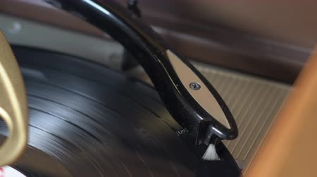 A classic old vinyl record turntable. The player starts, the needle adjusts for the record size, the vinyl drops and starts spinning, and the needle moves automatically to the start of the record.