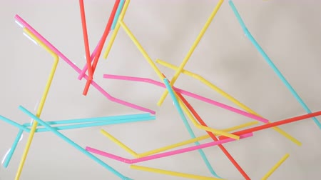 brightly colored plastic single use bendable straws tossed into water against a neutral white background
