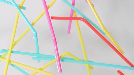 Close on brightly colored plastic single use bendable straws floating on the surface of water against a neutral white background