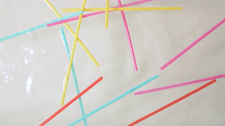 brightly colored plastic single use straws dropping into water against a neutral white background