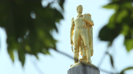 The gold Oregon Pioneer Man statue on top of the Oregon State Capitol building in Salem, seen through tree leaves and branches. Wideo