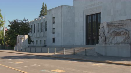 Outside the front of the Oregon Capitol building in Salem, the American flag waving at half-mast on the left. 2 large marble carvings of white settlers in frame the entrance steps. Stok Video
