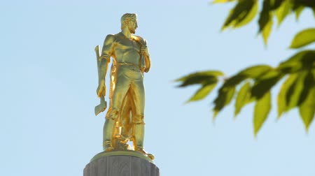 Орегон : The gold Oregon Pioneer Man statue on top of the Oregon State Capitol building in Salem, tree branches in the right of the frame. Стоковые видеозаписи