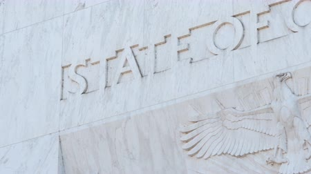 Pan across the text State Of Oregon and an eagle, stopping at the state name, engraved into marble above the main entrance to the Capitol Building in Salem. Wideo