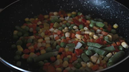 ervilhas : Stir fry frozen vegetables. Shaking the vegetables on skillet. Healthy cooking for dinner