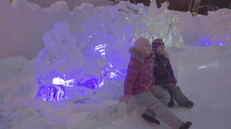igloo : People and baby Walk In Ice Town During Snowfall. Children plays at the igloo in Ice town, snow village.