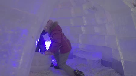 igloo : People and baby Walk In Ice Town During Snowfall. Children plays at the igloo in Ice town, snow village. .New Years Ice Town Illuminated .Ice and Snow World