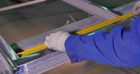 dekarz : A man measuring a part to make sure of the width before cutting it. a worker measures the frame for the window.Employee working with a protractor to make markings on a metal sheet. Tape measure. Work the sculptor makes drawings layout to the details with  Wideo