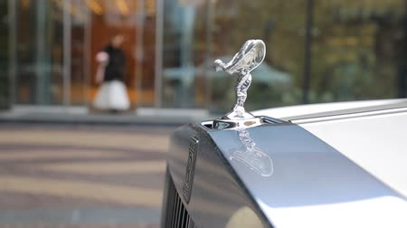 roll : Spirit of Ecstacy or Emily logo on the hood of a rolls Royce. and bride the background. Emmy or Spirit of Ecstacy, hood ornament of a Rolls Royce luxury car Stock Footage