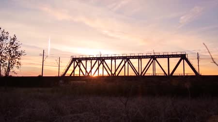 kormányoz : Panoramic view of train rides on rails through the bridge at sunrise. Timelapse. The train on the railway bridge.