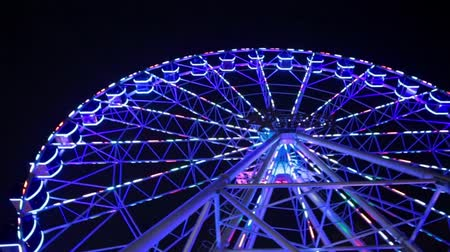 karnaval : Ferris wheel in blue neon light on dark background, Part of Ferris wheel with blue illumination against a black sky background at night. Ferris wheel by night. Ferris wheel with multi-colored illumination Stok Video