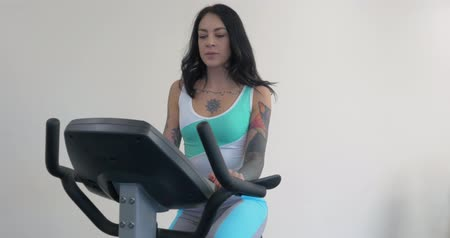 kolo : Three beautiful young women working out on bikes at the gym. Active young woman working out on exercise bike stationary bicycle. Sporty girl training at fitness hall, gym. Girl on Exercise bike, bicycle Dostupné videozáznamy