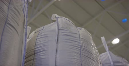 gmos : Warehouse for storage of fertilizers in bags. stack of big bag contain rice in warehouse. Big bags