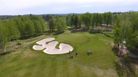 golfjátékos : Aerial view of golfers playing on putting green. Professional players on a green golf course.