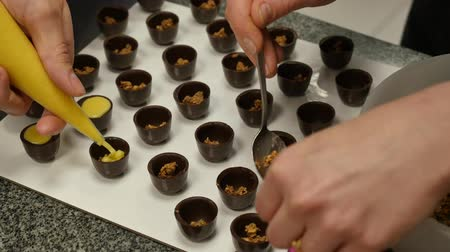 cukrozott : Closeup chefs hands decorate chocolate with cream and nuts. Women prepare sweets with cream and nuts