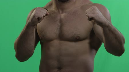 irritate : MMA fighter on a green screen. Muscular man on green screen. Green background. Man punching gesture