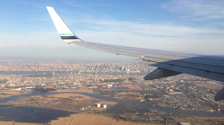 takeoff area : Looking trough window of an aircraft, airplane or plane wing. View from plane window during landing or takeoff over the city urban area